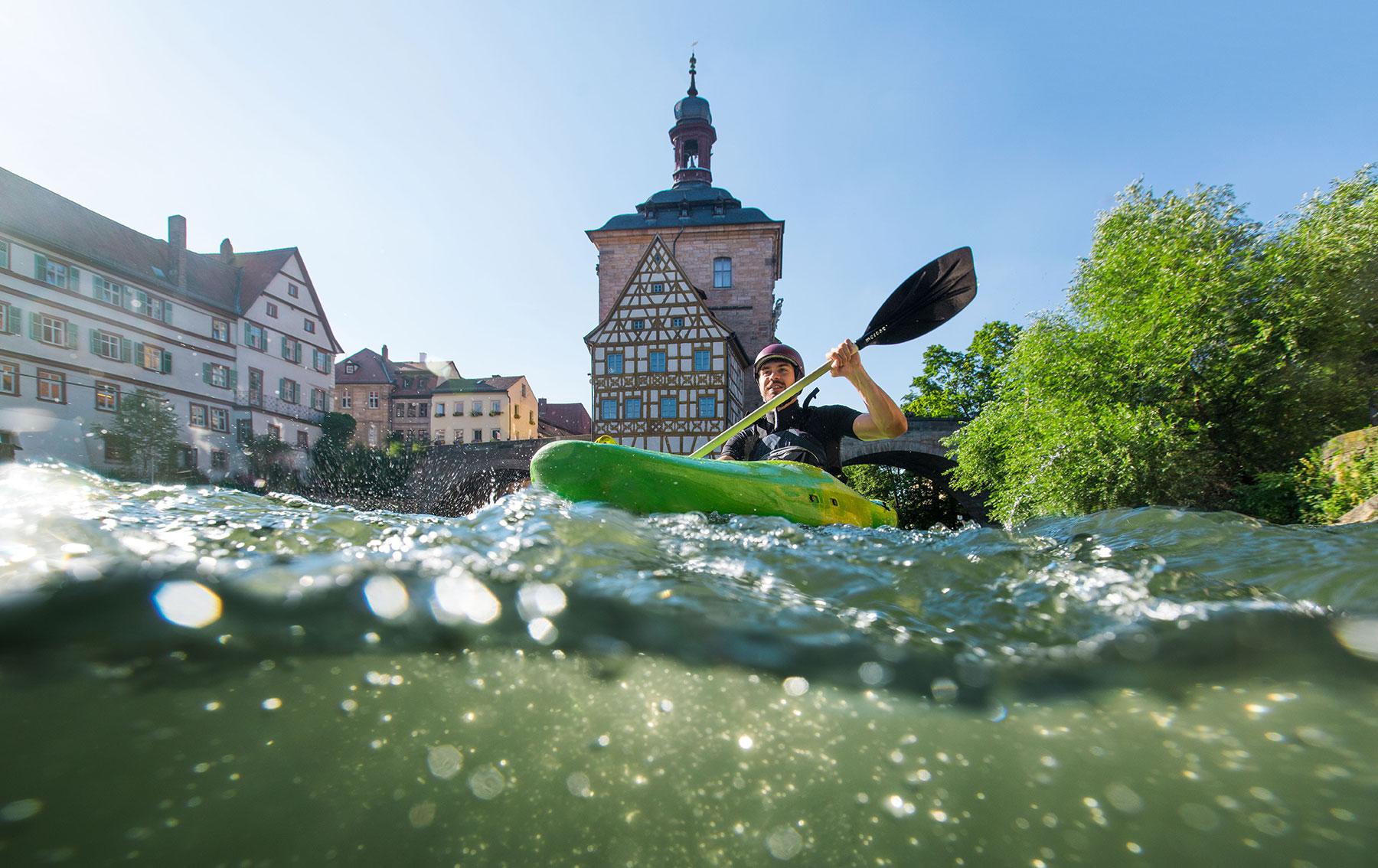 Kajakfahrer auf dem Wasserweg durch die historische Altstadt von Bamberg.