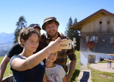 Familie macht Selfie vor Bauernhof.
