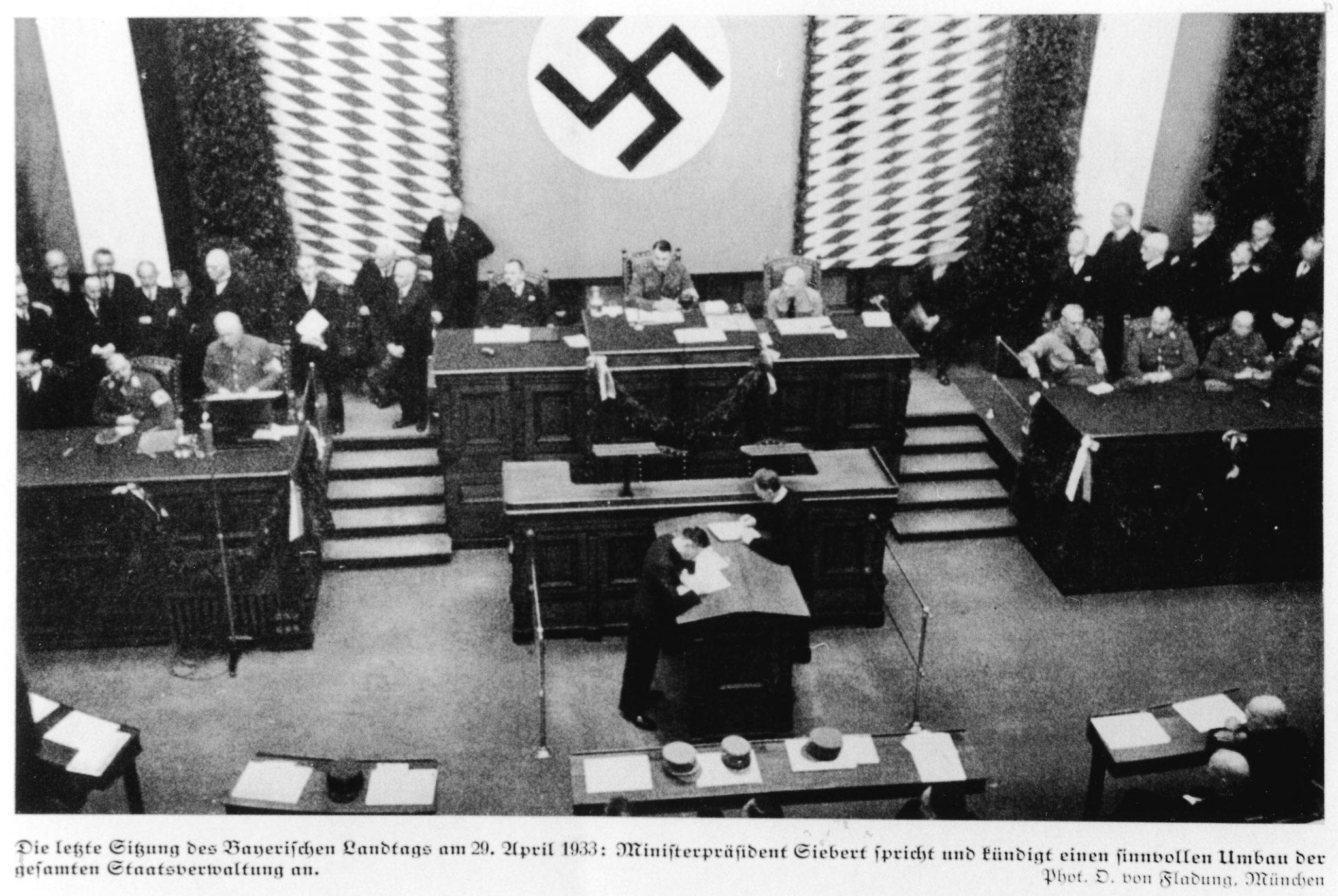 Abgeordnete tagen 1933 im Bayerischen Landtag. Das Hakenkreuz der Nationalsozialisten hängt im Hintergrund großflächig an der Wand.
