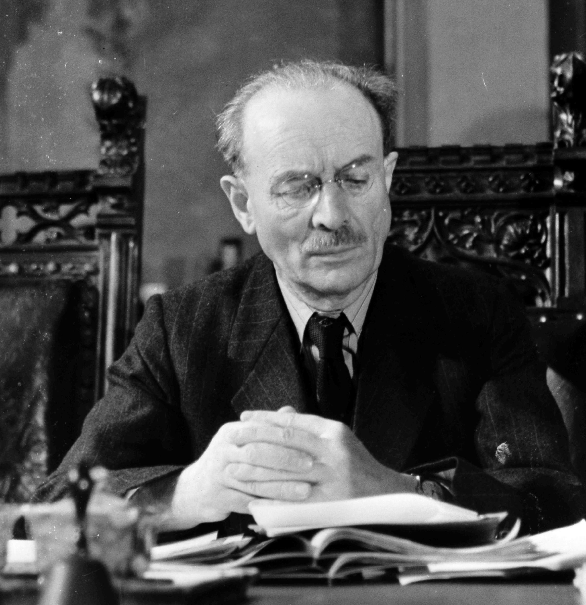 Ministerpräsident Wilhelm Hoegner von der SPD sitzt am Schreibtisch. Er blickt auf die vor ihm liegende Verfassung von 1946