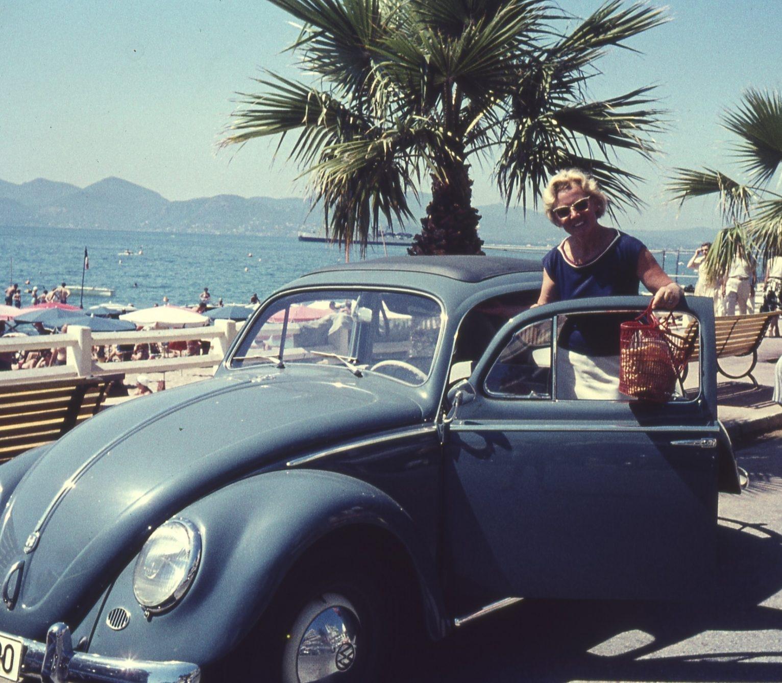 Frau steht neben ihrem Auto an der italienischen Riviera.