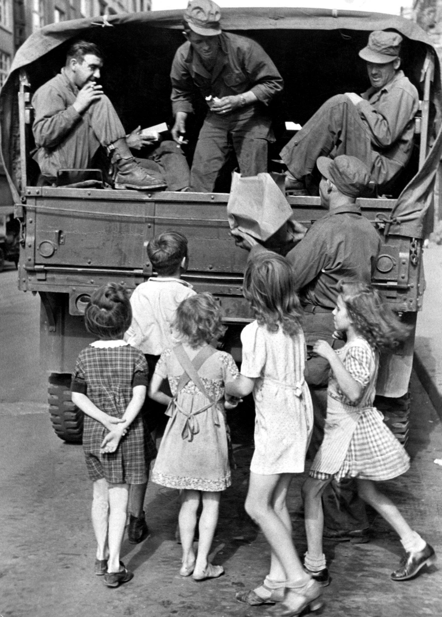 Amerikanische Soldaten verteilen Süßigkeiten an Kinder.