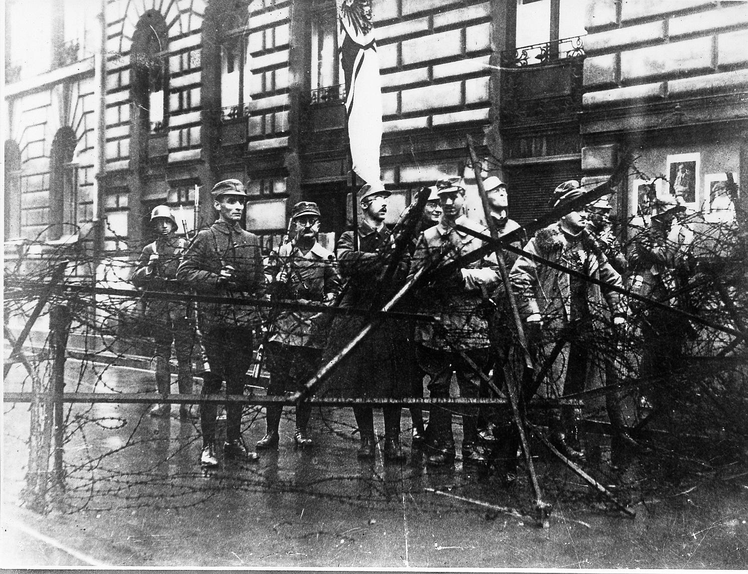 Nationalsozialisten unter ihnen Heinrich Himmler, hinter einer Straßenbarrikade in München.