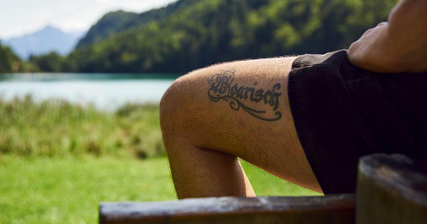 """Schriftzug """"Boarisch"""" tattowiert auf einem Oberschenkel, vor Landschaft"""