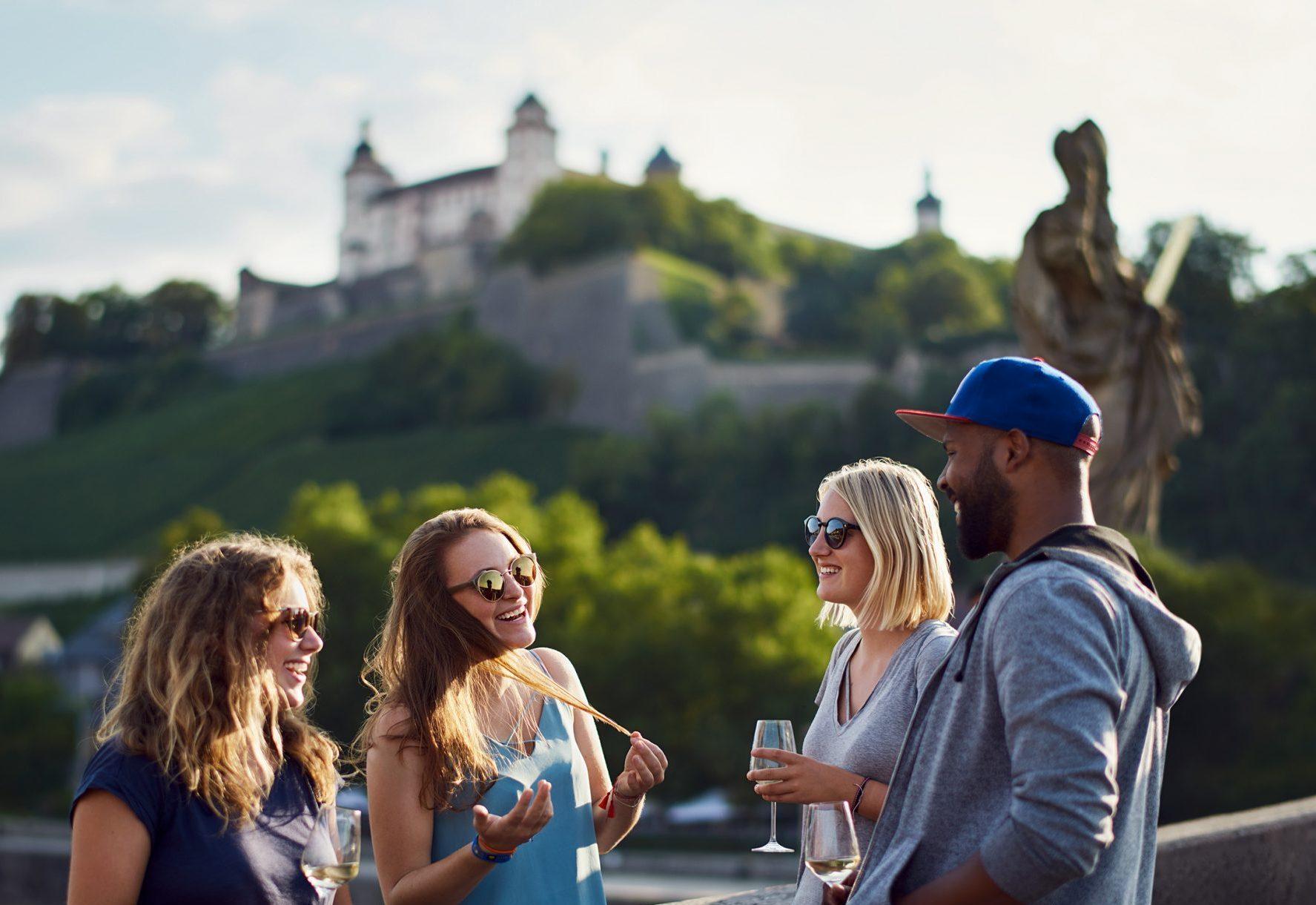 Junge Menschen unterhalten sich auf der Mainbrücke in Würzburg