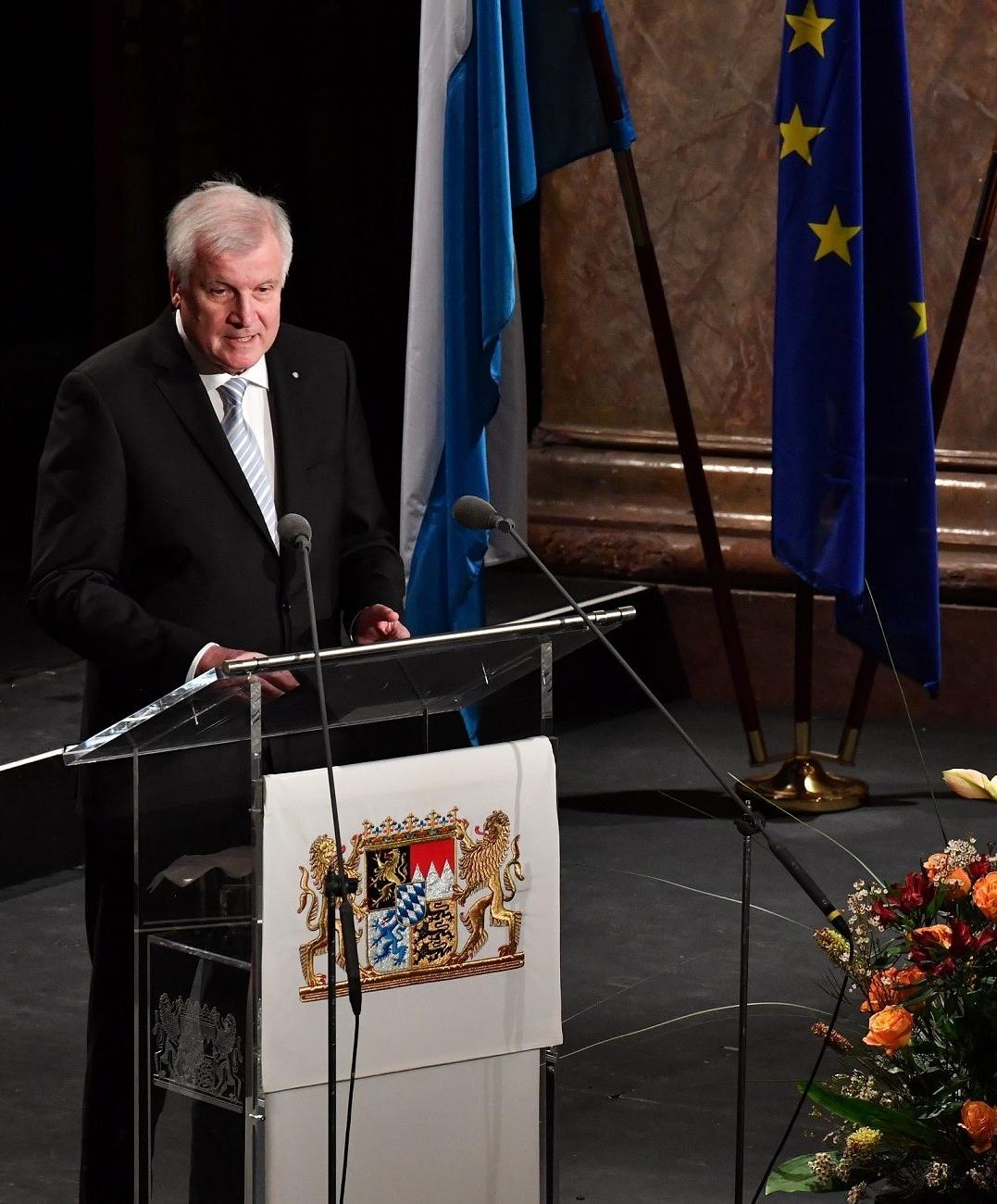 Vor dem Hintergrund der bayerischen und europäischen Flagge steht Ministerpräsident Horst Seehofer am Rednerpult beim Festakt im Nationaltheater in München am 1.12.2016.