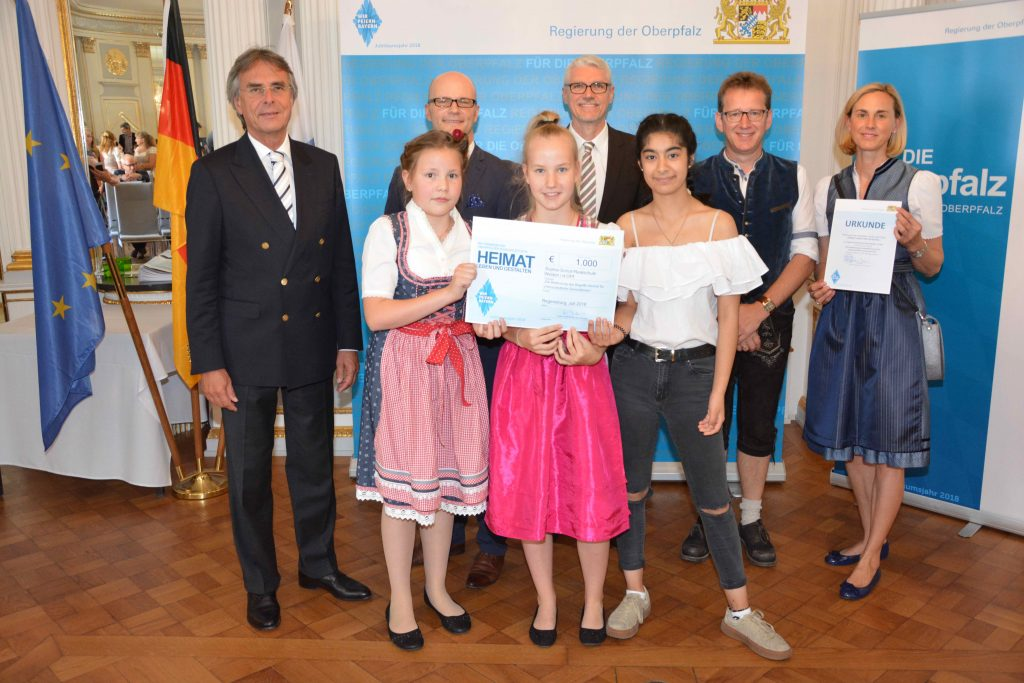 Regierungspräsident Axel Bartelt (l.), die Geehrten, Vertreter der Schulen und Ehrengäste aus der Stadt Weiden i.d.OPf.